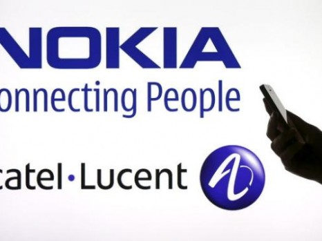 Photo illustration of a woman holding a smartphone in front of a screen displaying both Nokia and Alcatel Lucent logos in Paris